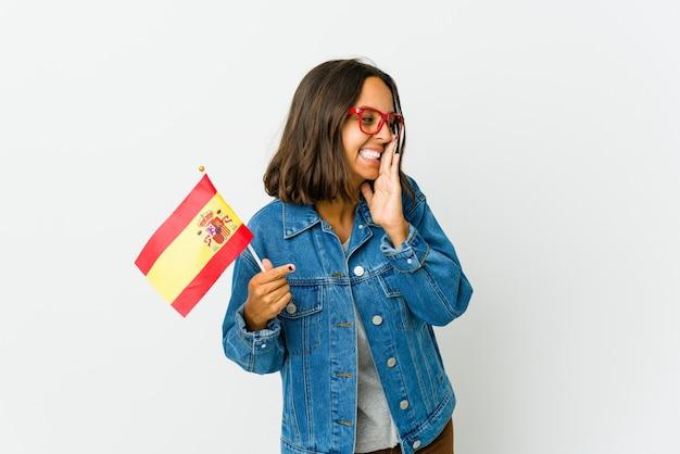 Junge spanische frau, die eine fahne lokalisiert auf weiß hält, die einen klatsch sagt und zur seite zeigt