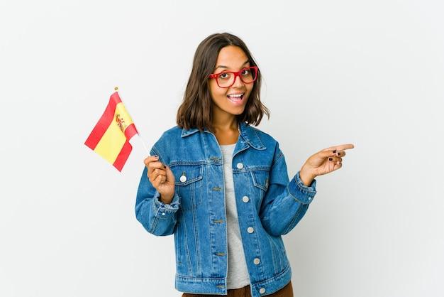 Junge spanische frau, die eine fahne lokalisiert auf weißer wand hält, die auf verschiedene kopienräume zeigt, einen von ihnen wählend, mit finger zeigend.