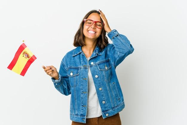Junge spanische frau, die eine flagge lokalisiert auf weißem hintergrund hält, lacht freudig, hände auf kopf haltend.