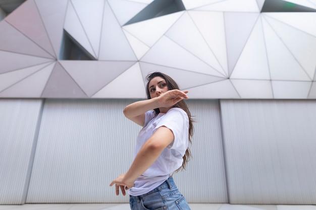 Junge spanische frau, die im nachbarschaftsplatz tanzt