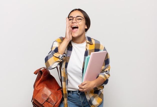Junge spanische frau, die sich glücklich, aufgeregt und positiv fühlt, einen großen schrei mit den händen neben dem mund gibt und ruft