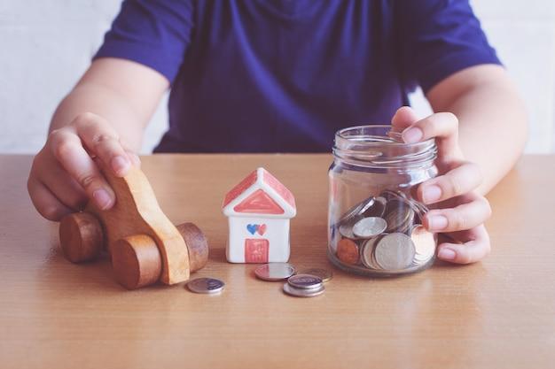 Junge spart geld für den kauf von haus und auto.