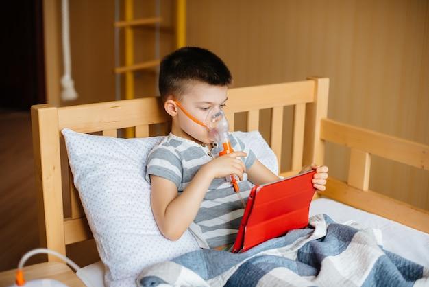Junge spielt auf einer tablette während eines lungeninhalationsverfahrens. medizin und pflege