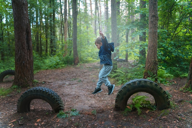Junge spielt im wald und springt über hindernisse