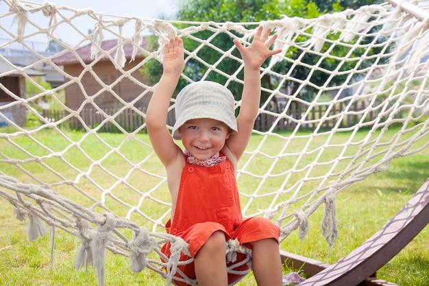 Junge spielt in der hängematte, glückliches kind.