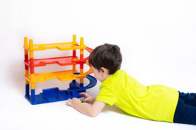 Junge spielt mit autos auf dem parkplatz. kinderspielzeug. ein junge spielt mit spielzeug an einer weißen wand. heller parkplatz für autos. glückliche kindheit