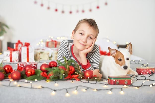 Junge spielt mit hund jack russell auf einem bett mit silvester dekoration