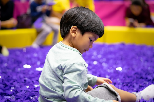 Junge spielt mit purpurrotem pädagogischem spielzeugblock