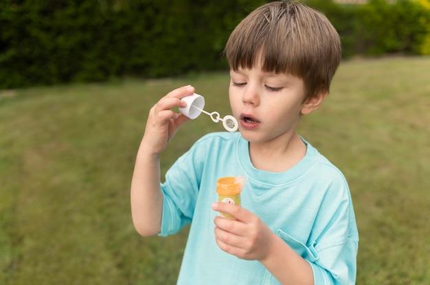 Junge spielt mit seifenblase