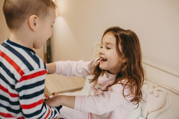 Junge spielt mit seiner fröhlichen größeren schwester im schlafzimmer