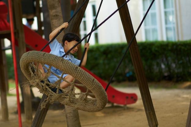 Junge spielt schaukel auf dem schulhof