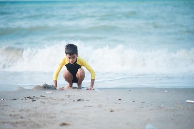 Junge spielt welle und sand am strand