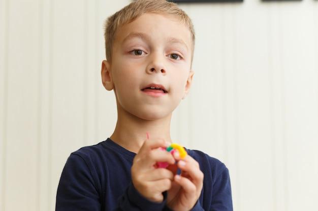Junge spinnt armband von gummiringen zu hause auf der couch