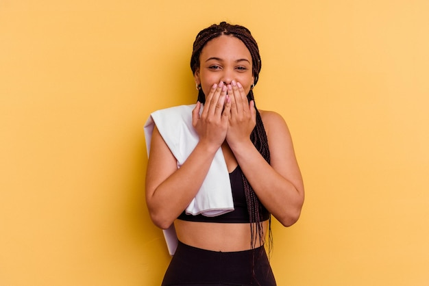 Junge sport-afroamerikanerfrau, die ein handtuch lokalisiert auf gelbem hintergrund hält, der über etwas lacht und mund mit händen bedeckt.