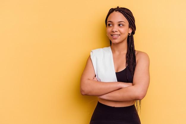 Junge sport afroamerikanerfrau, die ein handtuch lokalisiert auf gelber wand, die zuversichtlich mit verschränkten armen lächelt.