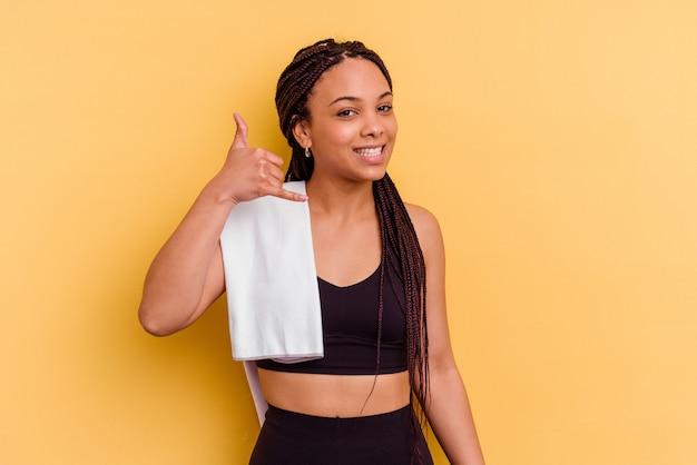 Junge sport-afroamerikanerfrau, die ein handtuch lokalisiert auf gelber wand hält, die eine handy-anrufgeste mit den fingern zeigt.