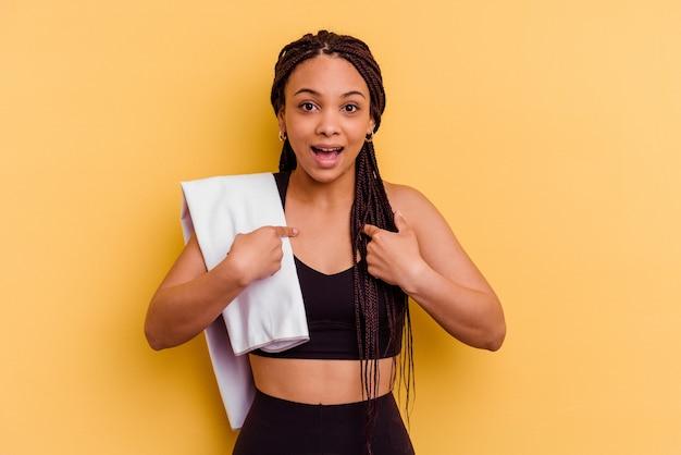 Junge sport-afroamerikanerfrau, die ein handtuch lokalisiert auf gelber wand hält, überrascht mit dem finger zeigend, breit lächelnd.