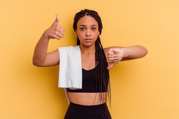 Junge sport-afroamerikanerfrau, die ein handtuch lokalisiert auf gelber wand zeigt, die daumen oben und daumen unten zeigt, schwieriges auswahlkonzept