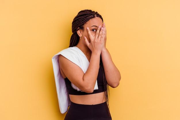Junge sport-afroamerikanerfrau, die ein handtuch lokalisiert auf gelber wandblink durch finger verängstigt und nervös hält.