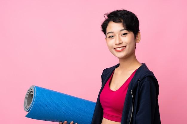 Junge sport asiatin über lokalisierter rosa wand mit einer matte und einem lächeln