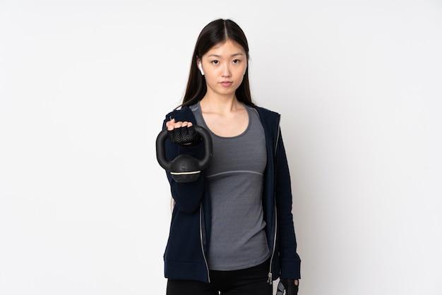 Junge sport asiatische frau auf weißer wand, die gewichtheben mit kettlebell macht und schaut