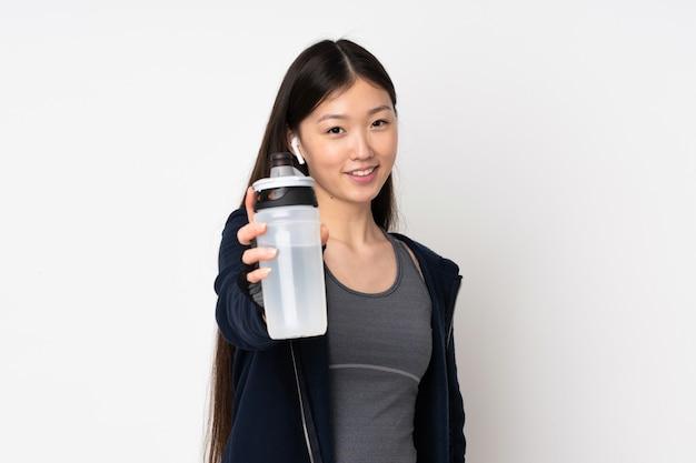 Junge sport asiatische frau auf weißer wand mit sportwasserflasche