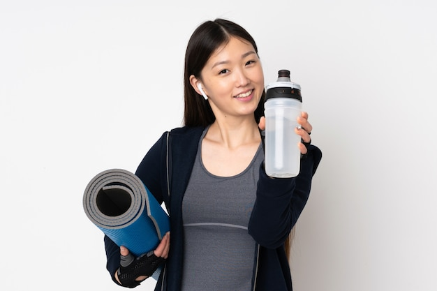 Junge sport asiatische frau lokalisiert auf weißer wand mit sportwasserflasche und mit einer matte