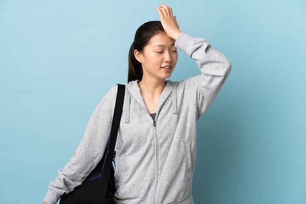 Junge sport-chinesin mit sporttasche auf isoliertem blau hat etwas erkannt und beabsichtigt die lösung
