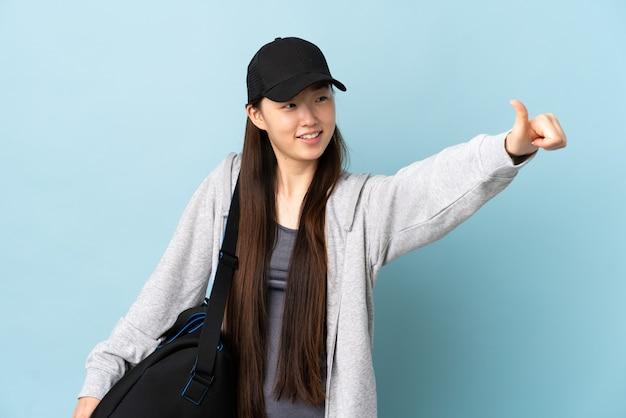 Junge sport-chinesin mit sporttasche über blau, die eine daumen hoch geste gibt