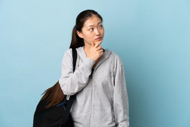 Junge sport-chinesin mit sporttasche über blauer wand, die zweifel hat