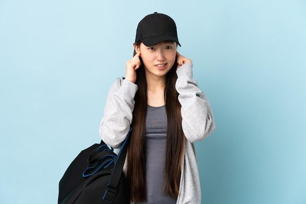 Junge sport-chinesin mit sporttasche über isolierte blaue wand frustriert und ohren bedeckend