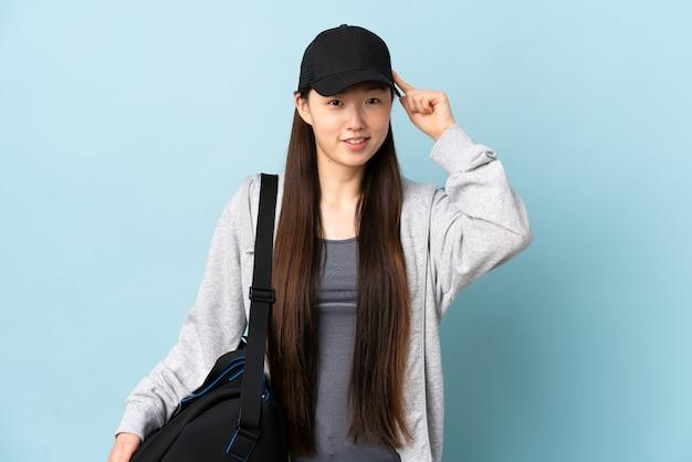 Junge sport-chinesin mit sporttasche über isoliertem blau, das zweifel und denken hat