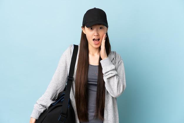 Junge sport-chinesin mit sporttasche über isoliertem blau mit überraschung und schockiertem gesichtsausdruck