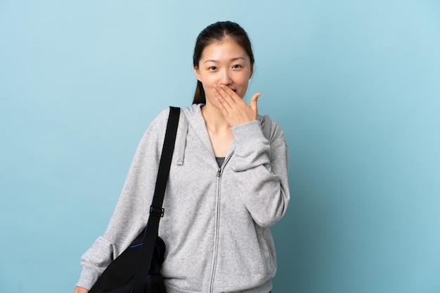 Junge sport-chinesin mit sporttasche über isoliertem blauem glücklichem und lächelndem bedeckendem mund mit hand