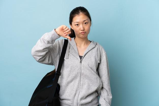 Junge sport-chinesin mit sporttasche über isolierter blauer wand, die daumen unten mit negativem ausdruck zeigt