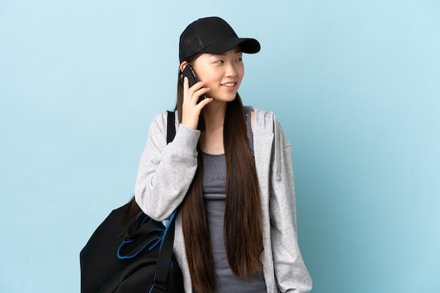Junge sport-chinesin mit sporttasche über isolierter blauer wand, die ein gespräch mit dem mobiltelefon mit jemandem hält