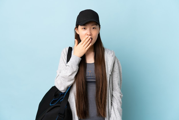 Junge sport-chinesin mit sporttasche über isolierter blauer wand, die gähnt und weit geöffneten mund mit hand bedeckt