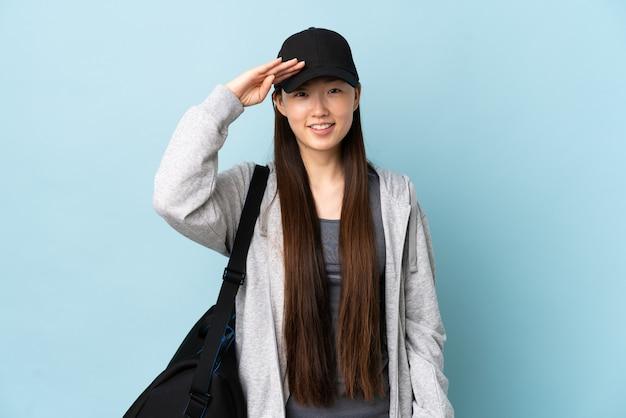 Junge sport-chinesin mit sporttasche über isolierter blauer wand, die mit hand mit glücklichem ausdruck salutiert