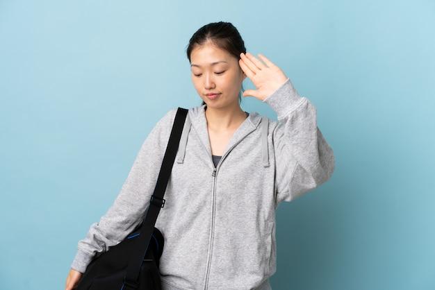 Junge sport-chinesin mit sporttasche über isolierter blauer wand, die stoppgeste und enttäuscht macht