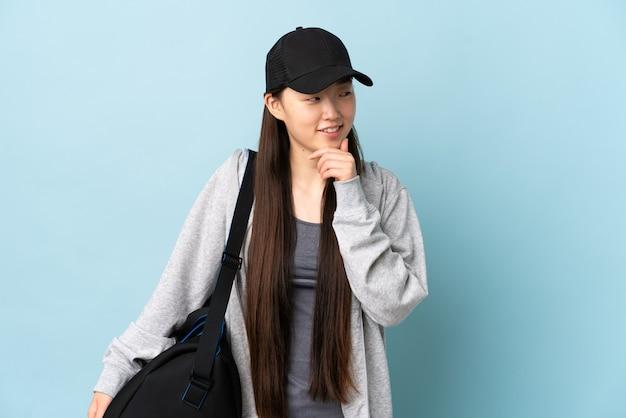 Junge sport-chinesin mit sporttasche über isolierter blauer wand, die zur seite schaut und lächelt