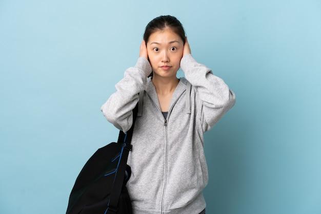 Junge sport-chinesin mit sporttasche über isolierter blauer wand frustriert und ohren bedeckend
