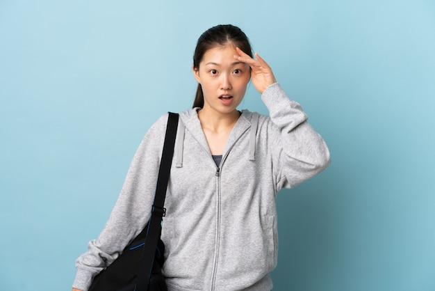 Junge sport-chinesin mit sporttasche über isolierter blauer wand hat etwas erkannt und beabsichtigt die lösung