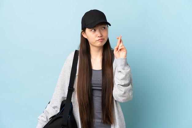 Junge sport-chinesin mit sporttasche über isolierter blauer wand mit den fingern kreuzend und wünschend das beste