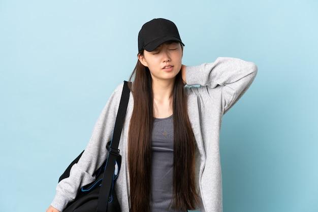 Junge sport-chinesin mit sporttasche über isolierter blauer wand mit nackenschmerzen