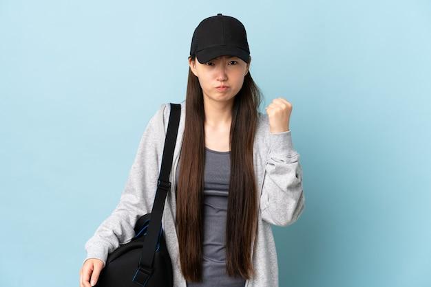 Junge sport-chinesin mit sporttasche über isolierter blauer wand mit unglücklichem ausdruck