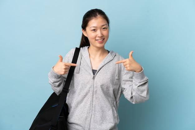 Junge sport-chinesin mit sporttasche über isolierter blauer wand stolz und selbstzufrieden