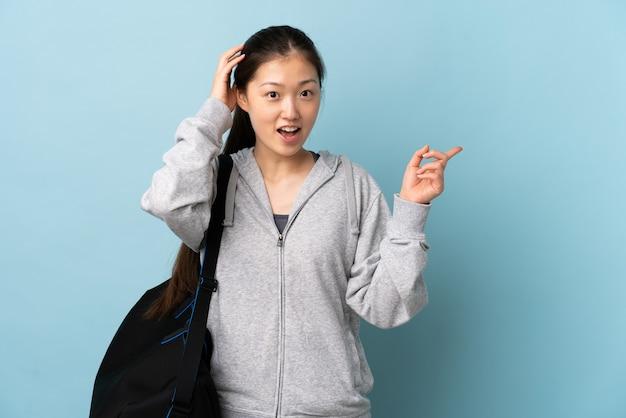 Junge sport-chinesin mit sporttasche über isolierter blauer wand überrascht und finger zur seite zeigend