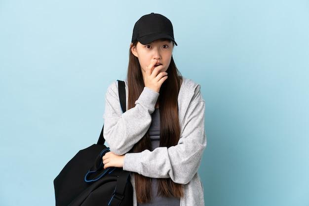 Junge sport-chinesin mit sporttasche über isolierter blauer wand überrascht und schockiert, während sie nach rechts schaut