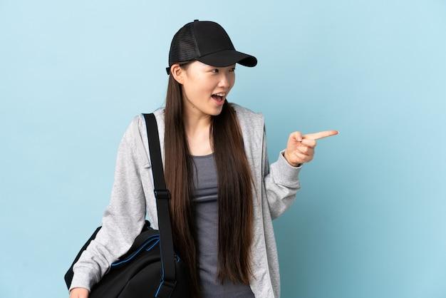 Junge sport-chinesin mit sporttasche über lokalisiertem blau zeigendem finger zur seite und präsentieren eines produkts