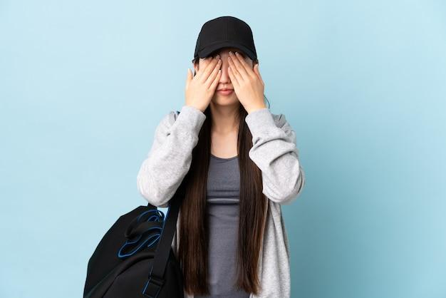 Junge sport-chinesin mit sporttasche über lokalisiertem blauem hintergrund, der augen durch hände bedeckt